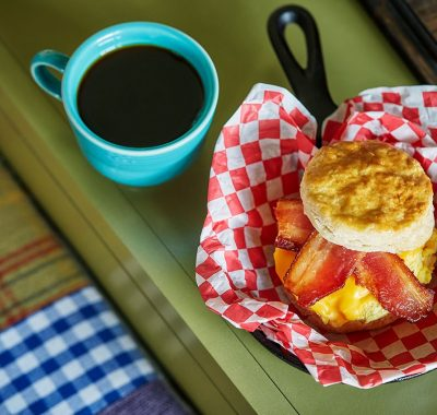 basket with a biscuit sandwich and a cup of coffee