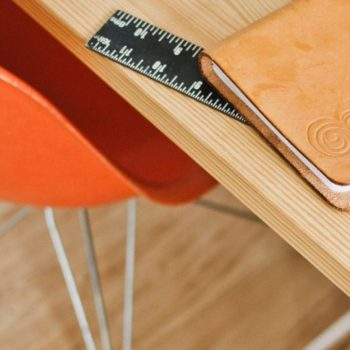 Desk with right angle ruler, notebooks and a copic pen
