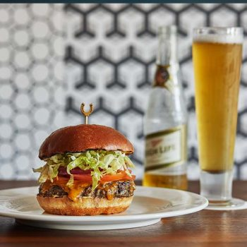 burger on a plate and a tall glass of beer
