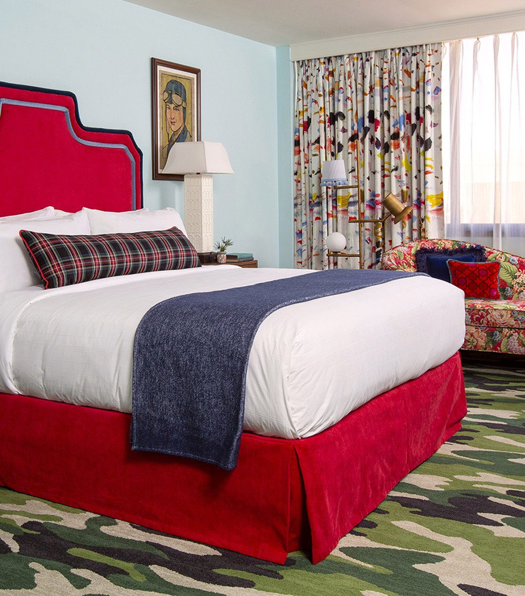 Guestroom at Graduate Fayetteville, featuring a red headboard and camo carpet.