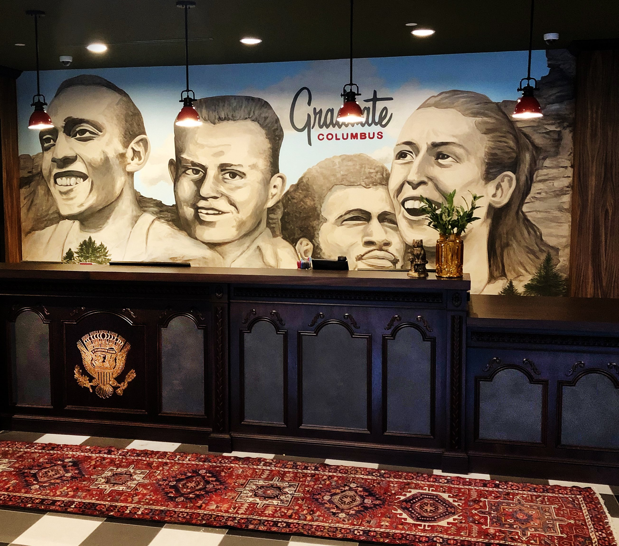 Front desk at Graduate Columbus with a mural of Ohio athletes